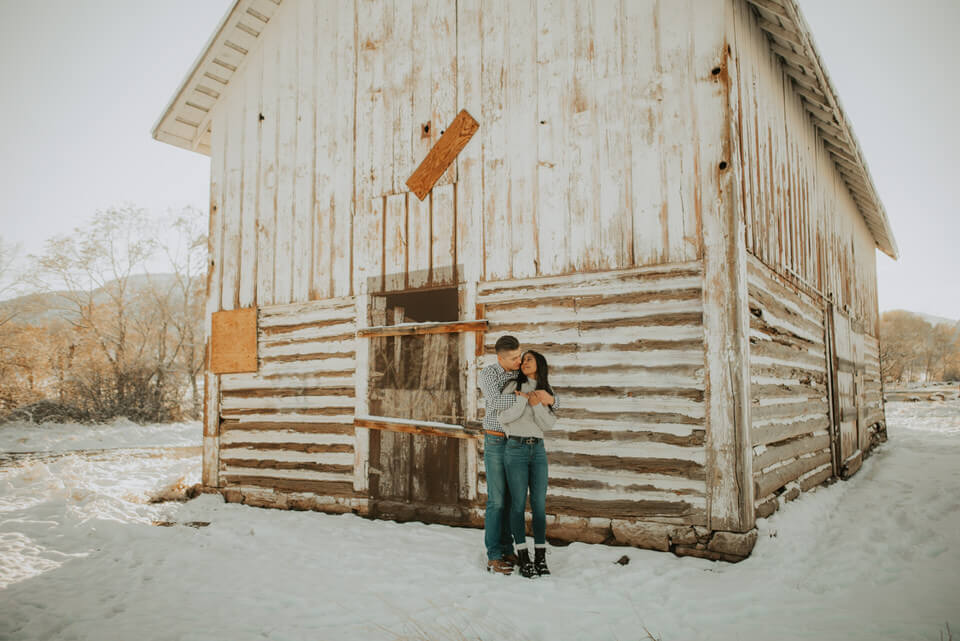 couples engagement photos in front of barn in the snow at deer creek in littleton colorado