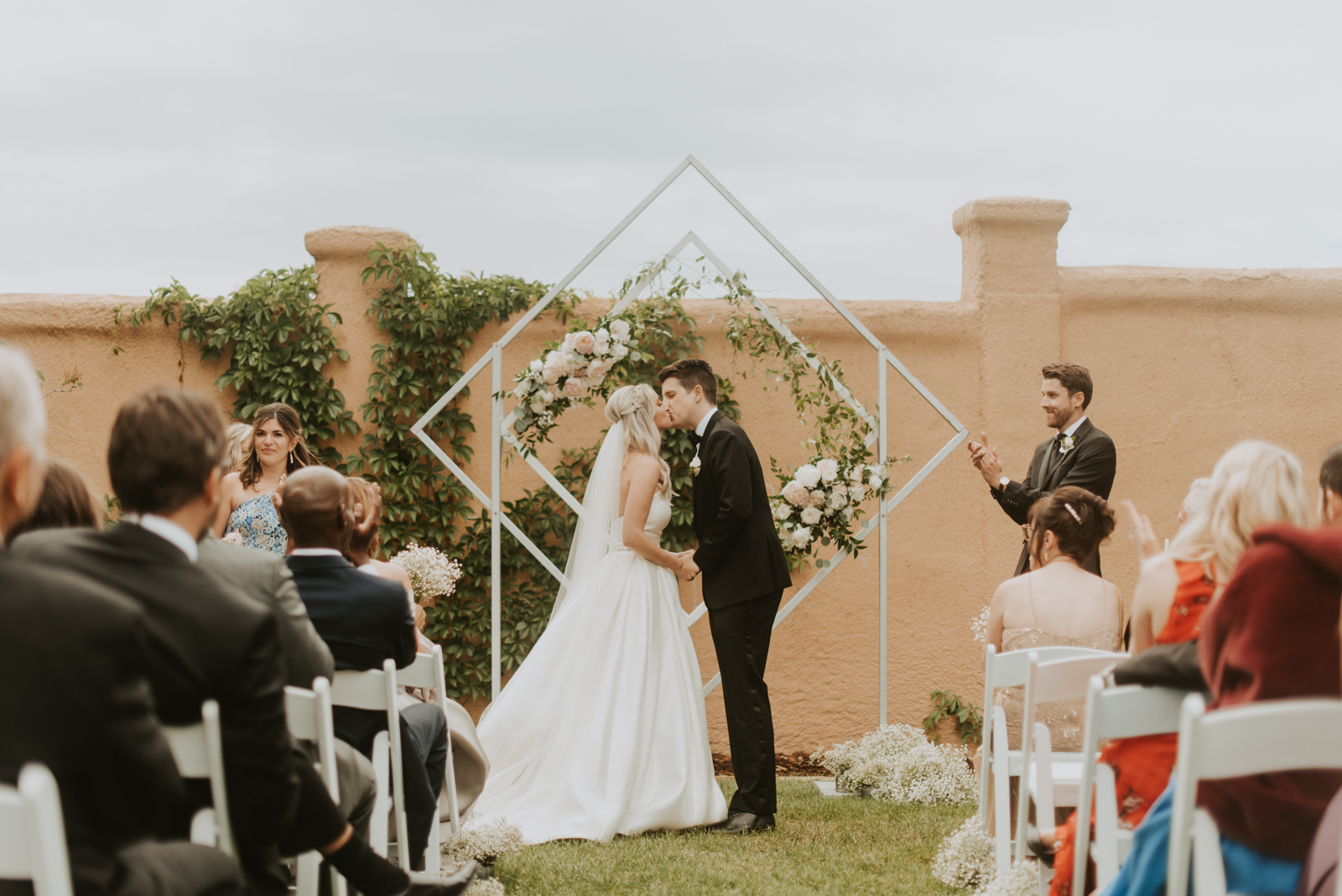 bride and groom have their first kiss in front of their white and floral geometric wedding arch in Parker, Colorado.