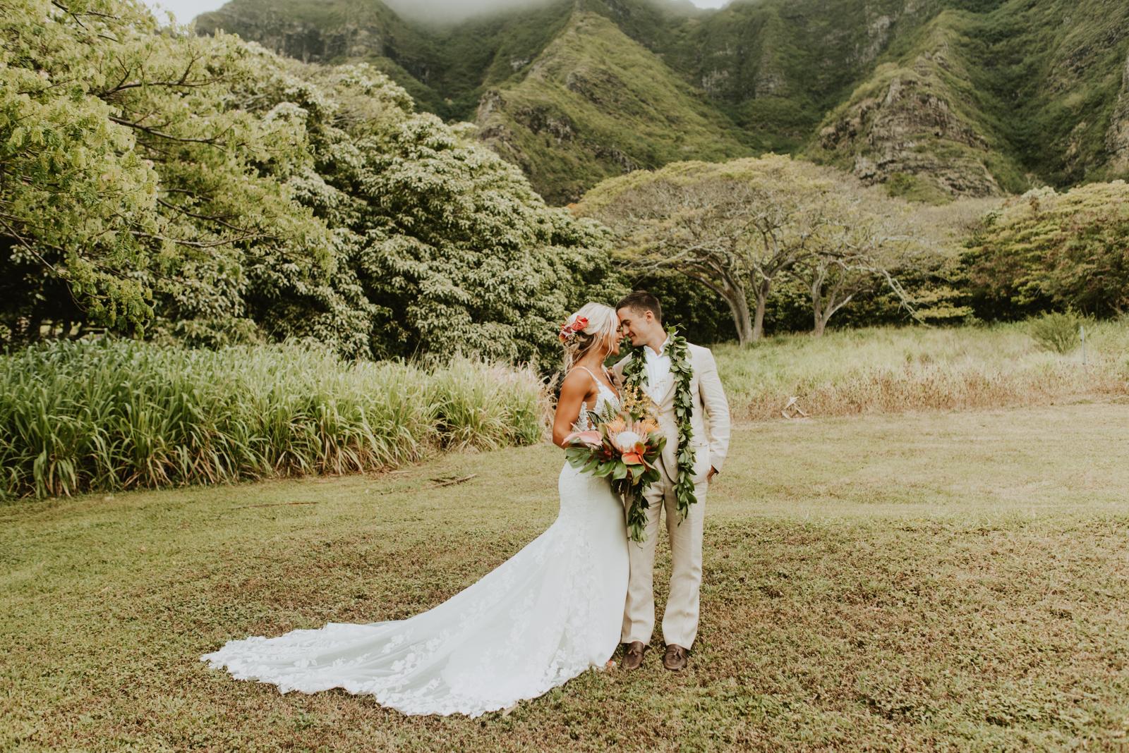 bride and groom at their tropical boho wedding at kualoa ranch in oahu, hawaii
