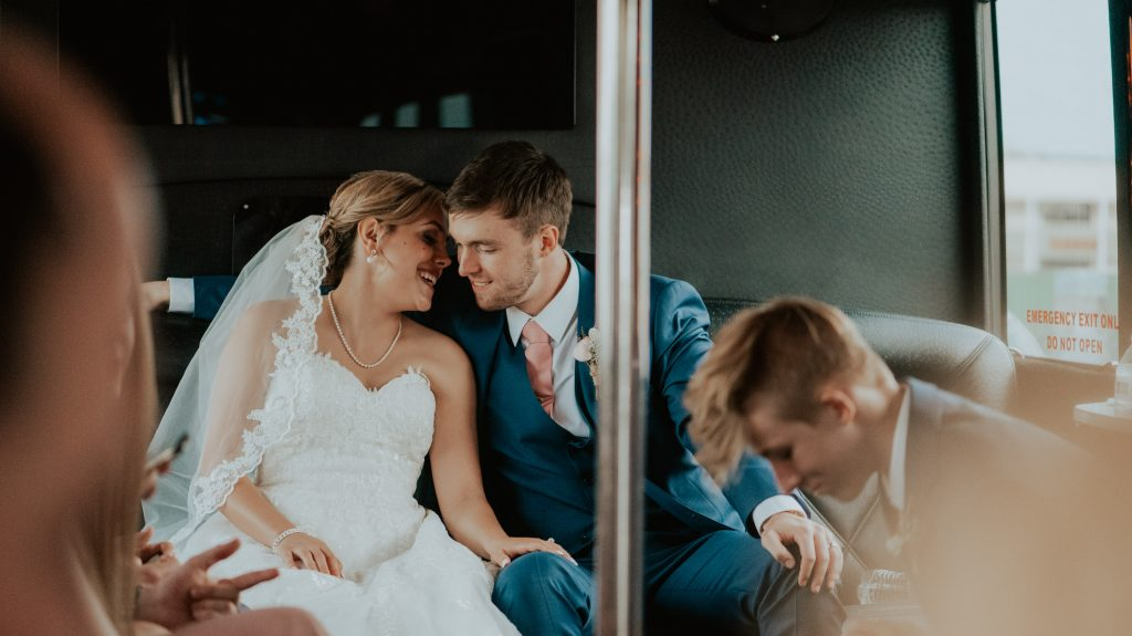 bride and groom on party bus after ceremony from church wedding in denver, colorado