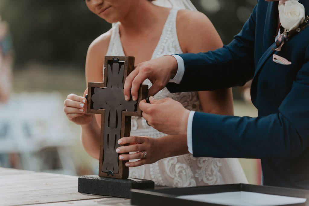 bride and groom building cross at ceremony from omaha nebraska barn at ackerhurst wedding