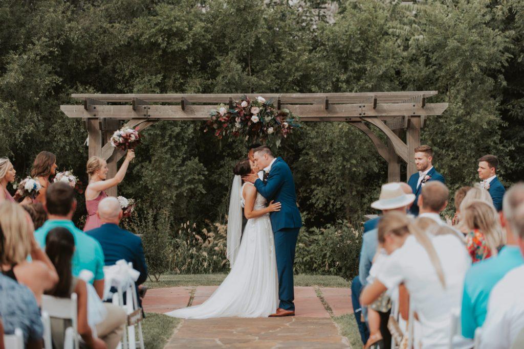bride and groom kiss at ceremony from omaha nebraska barn at ackerhurst wedding