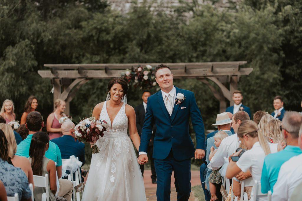 bride and groom exit at ceremony from omaha nebraska barn at ackerhurst wedding
