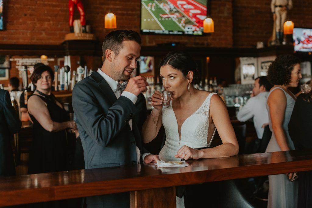 bride and groom taking shots at sullivans bar in omaha nebraska