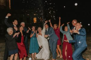 family and bride and groom popping champagne at wedding day in lincoln nebraska